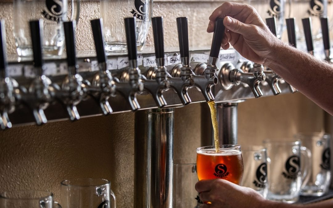 Satire Brewing Company Denver, CO- Man pouring beer into glass.