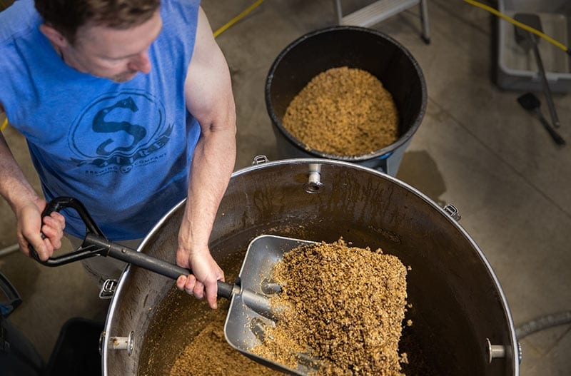 Brewing Beer Denver, Colorado- Owner putting hops in beer barrel