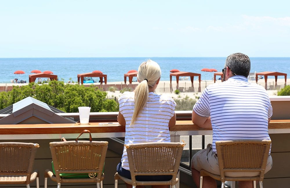Couple Looking At Atlantic Ocean from Harry's Ocean Bar & Grille Rooftop.