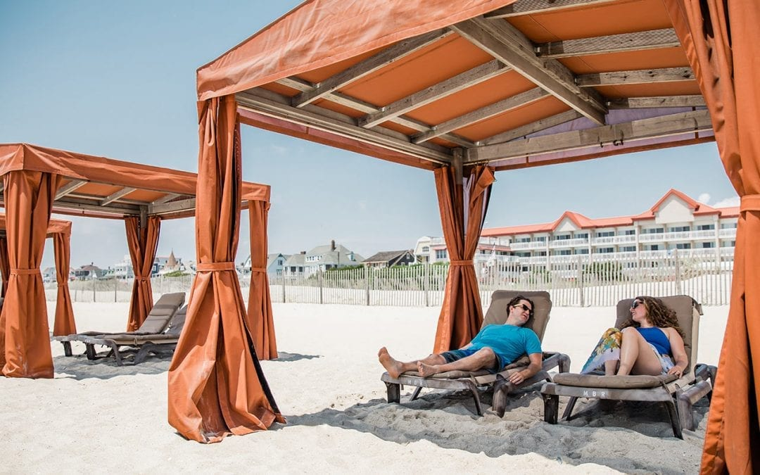 Couple relaxing in beach cabana in front of Montreal Beach Resort.