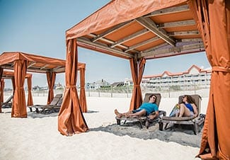 couple lounging in cabana in front of Montreal Beach Resort Cape May NJ Resort