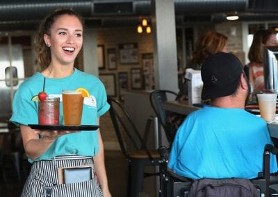 Waitress smiling while carrying drinks on platter at Harrys Bar
