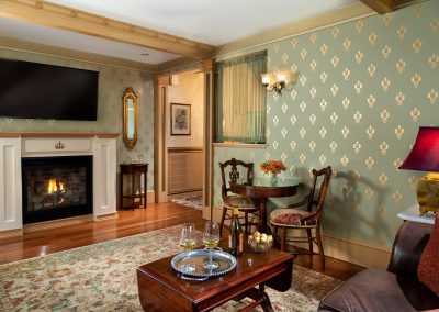 Photo of the Crown Jewel suite parlor with big screen TV above a custom made lit gas log fireplace