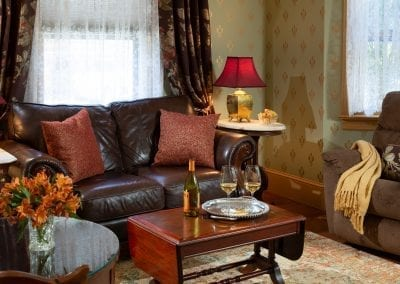 Crown Jewel Sitting Room with Leather Sofa, Reclining Chair and Wine Glasses on the Coffee Table