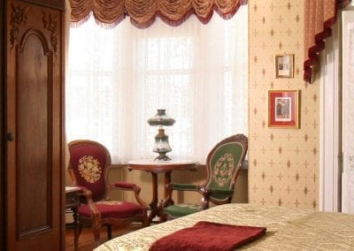 The Queen Victoria guestroom bay window sitting area with two antique embroidered chairs