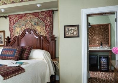 Close up of Crown Prince Guestroom's Elegant Solid Wood King headboard with beautiful tapestry behind it. Also a closeup of the hall into the guestroom's private sitting room with wetbar.