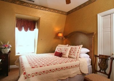 Princess Beatrice guestroom queen bed, antique side chair and dresser.