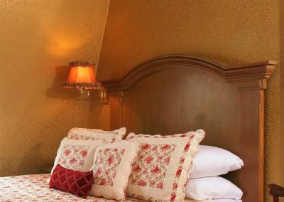 Princess Beatrice guestroom queen bed featuring a burgundy floral quilt and pillows