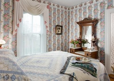 Lillie Langtry guestroom bedroom with queen bed and antique mirrored dresser. Pink and blue floral wallpaper.