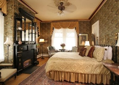 Osborne Guestroom with Queen Bed and dramatic original black carved wood mantle with marble inlay accents.