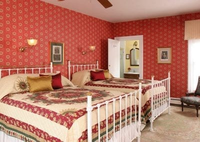 Prince Albert guestroom with rich red wallpaper and two queen beds with white iron bed frames. Beds have traditional red, gold and green quilts