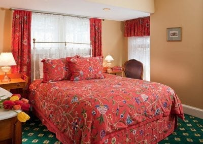 Regents Park bedroom with vibrant red floral crewel stitched bedding and draperies.