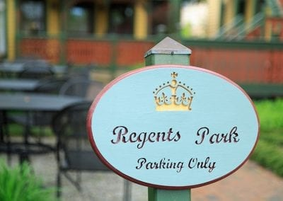 """Photo of an oval green and burgundy """"Regents Park Parking Only """" sign"""