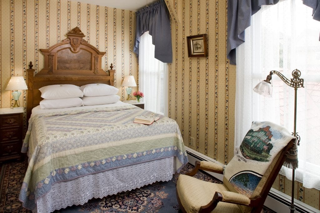 The Charles Dickens guestroom bedroom with a queen bed with a beautiful blue and purple quilt. The solid wood antique headboard is stately.