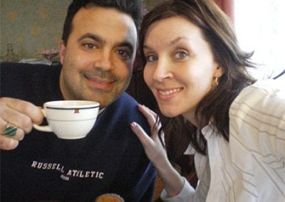 Guest Photos- Closeup of young couple smiling. Man holding coffee cup.