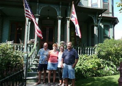 Guest Photos- Two couples standing outside of Queen Victoria below flags.