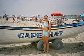 Guest Photos- Girl standing next to small boat at beach.