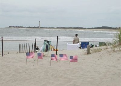 Small American flags on beach with people near ocean.